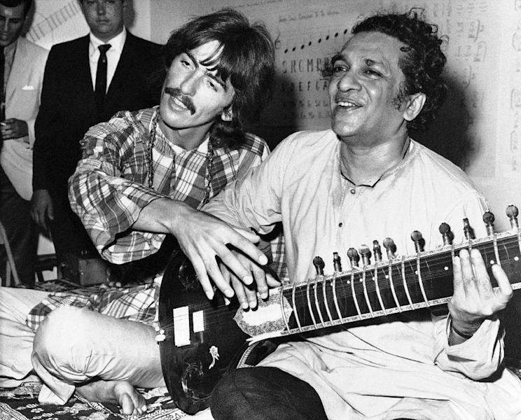 FILE - In this Aug. 3, 1967 file photo, George Harrison, of the Beatles, left, sits cross-legged with his musical mentor, Ravi Shankar of India, in Los Angeles, as Harrison explains to newsmen that Shankar is teaching him to play the sitar. Shankar, the sitar virtuoso who became a hippie musical icon of the 1960s after hobnobbing with the Beatles and who introduced traditional Indian ragas to Western audiences over an eight-decade career, died Tuesday, Dec. 11, 2012. He was 92. (AP File Photo)