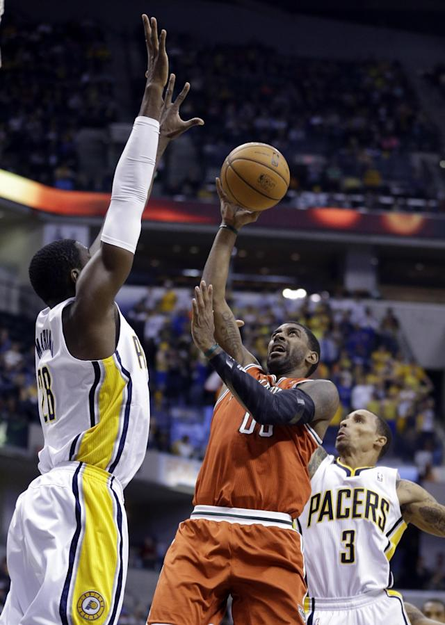Milwaukee Bucks guard O.J. Mayo, center shoots between Indiana Pacers center Ian Mahinmi, left, and guard George Hill in the first half of an NBA basketball game in Indianapolis, Friday, Nov. 15, 2013. (AP Photo/Michael Conroy)