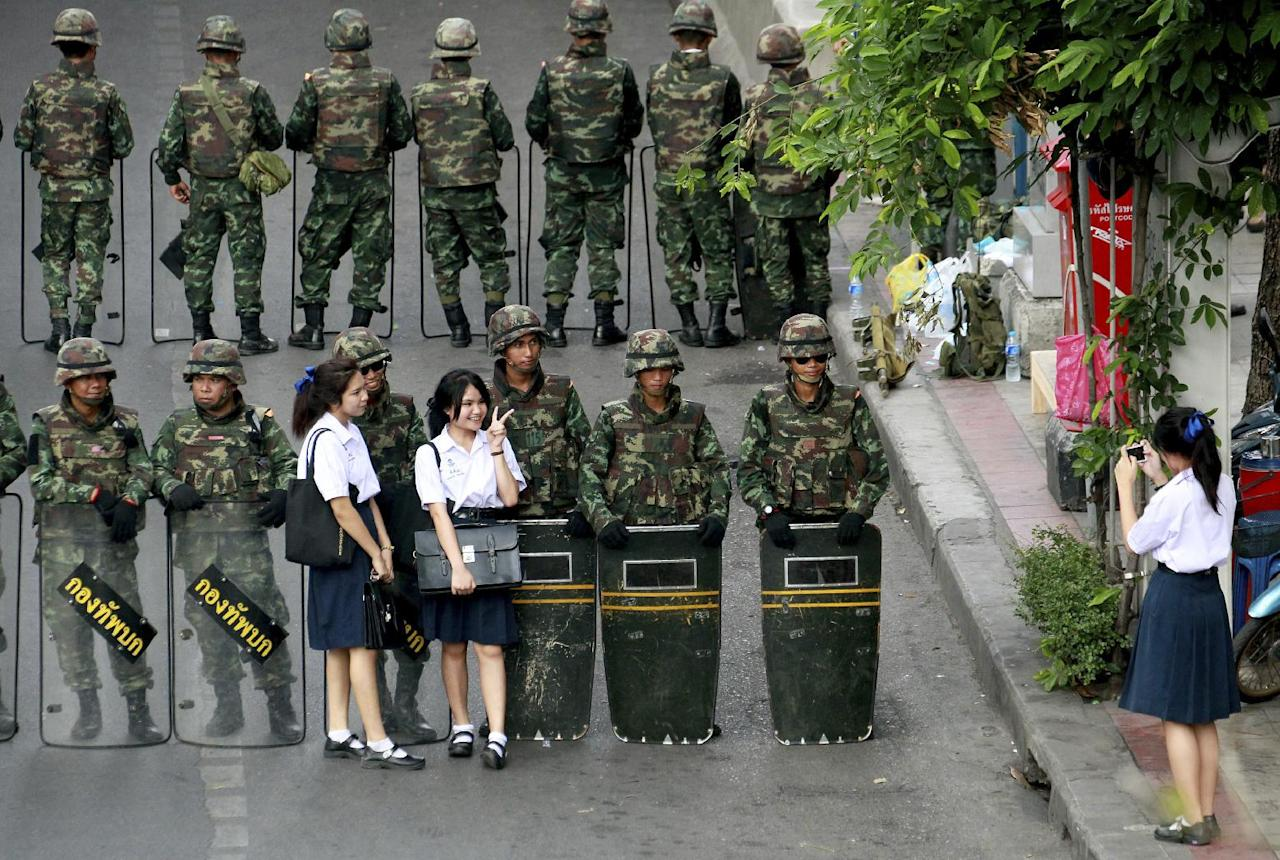 Thai school girls have their photographs taken with soldiers guarding the area to prevent anti-coup demonstration at Victory Monument in Bangkok, Thailand Thursday, May 29, 2014. More than 1,000 Thai troops and police sealed off one of Bangkok's busiest intersections Thursday to prevent a planned protest, as authorities said they would no longer allow any demonstrations against last week's military coup. (AP Photo/Wason Wanichakorn)