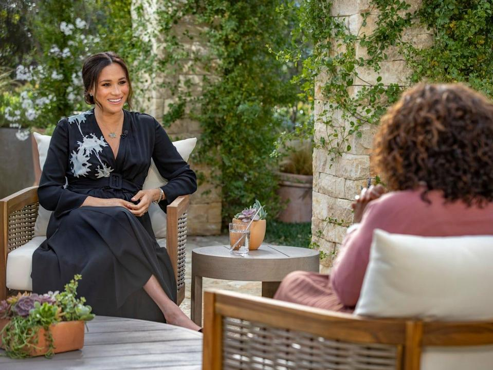 Meghan Markle sitting across from Oprah Winfrey outside during a taped interview.