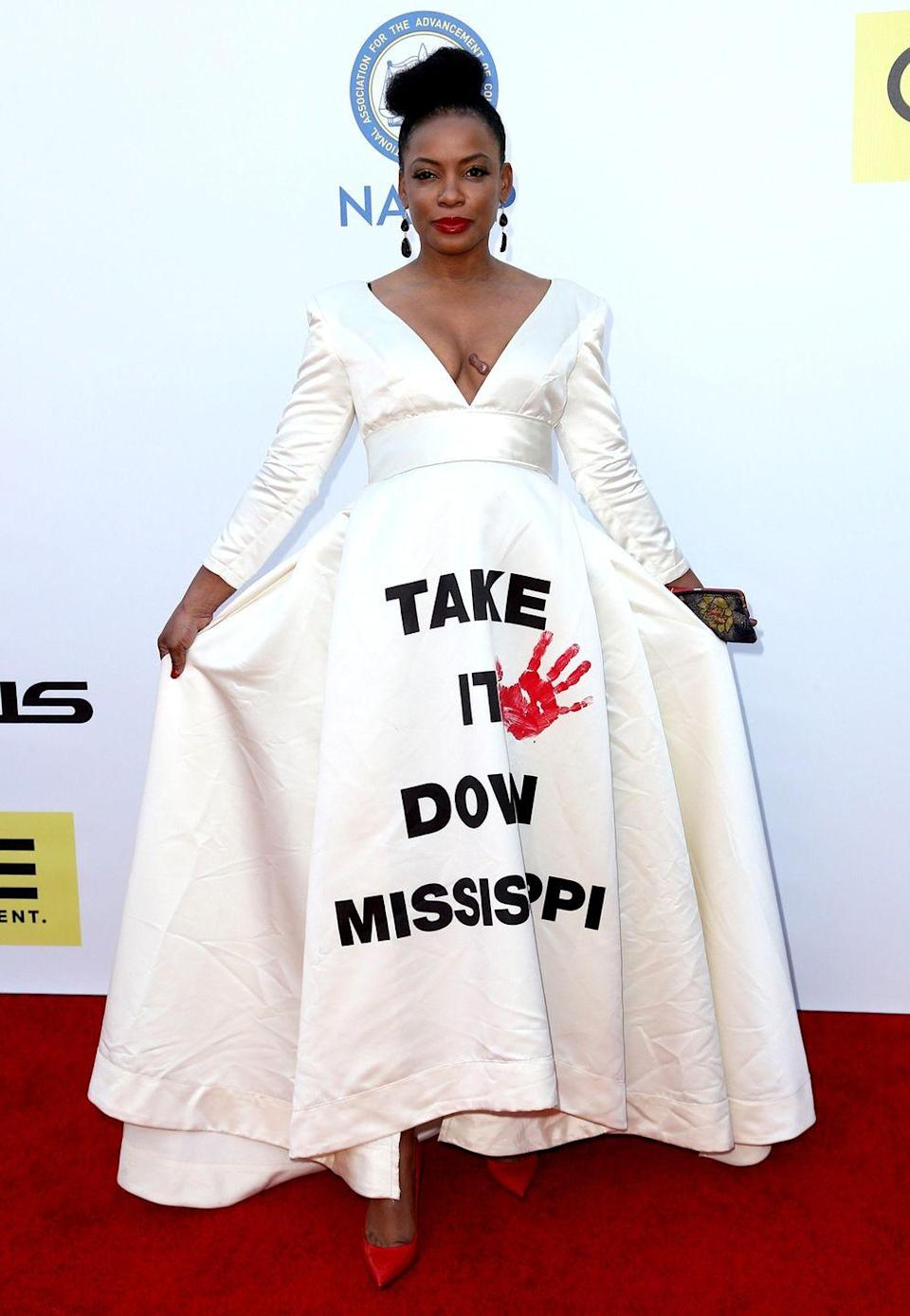 """<p>Actress Aunjanue Ellis wore this <a href=""""https://www.bet.com/news/celebrities/2016/02/06/everyone-is-talking-about-aunjanue-ellis--naacp-aw.html"""" rel=""""nofollow noopener"""" target=""""_blank"""" data-ylk=""""slk:statement-making dress"""" class=""""link rapid-noclick-resp"""">statement-making dress</a> to the 2016 NAACP Image Awards. The dress was emblazoned with """"Take it down Mississippi,"""" which was a reference to the the use of the confederate battle emblem on the official state flag at the time. In 2020, lawmakers voted to <a href=""""https://www.nytimes.com/2020/06/30/us/mississippi-flag.html"""" rel=""""nofollow noopener"""" target=""""_blank"""" data-ylk=""""slk:change Mississippi's state flag"""" class=""""link rapid-noclick-resp"""">change Mississippi's state flag</a>. </p>"""