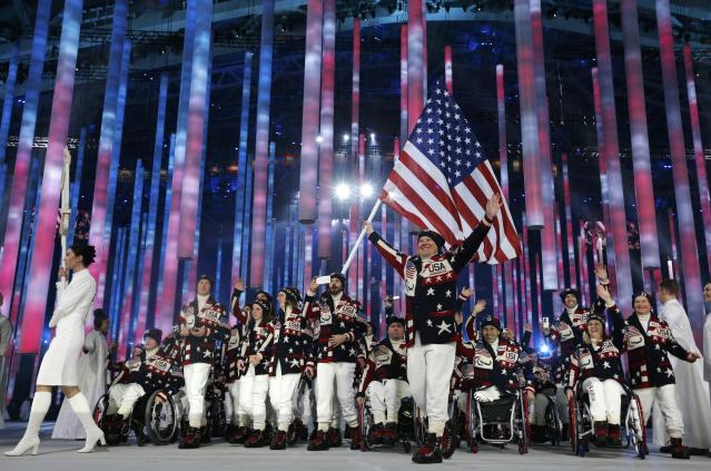 Flag-bearer Jonathan Lujan of the U.S. (C), leads his country's contingent during the opening ceremony of the 2014 Paralympic Winter Games in Sochi, March 7, 2014. REUTERS/Alexander Demianchuk (RUSSIA - Tags: OLYMPICS SPORT TPX IMAGES OF THE DAY)