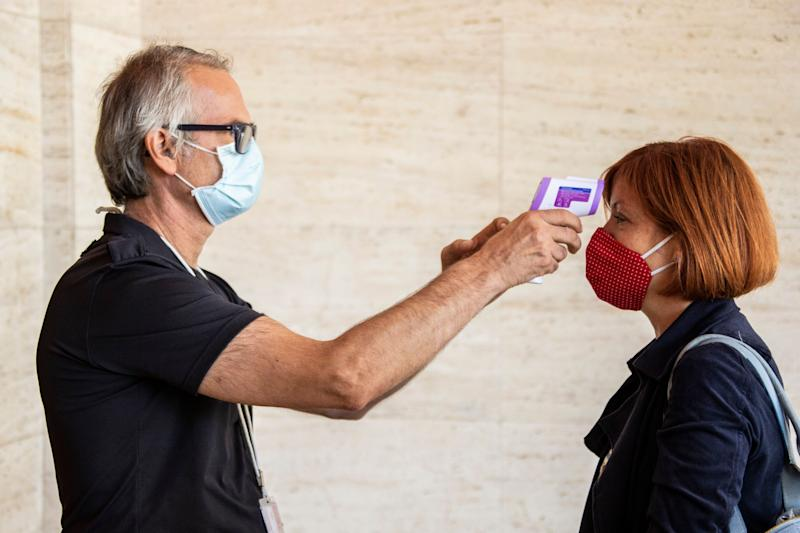 A festival attendee has their temperature checked ahead of the start of the 77th edition of the Venice Film Festival in Venice, Italy, Tuesday, Sept. 1, 2020. Italy was among the countries hardest hit by the coronavirus pandemic, and the festival will serve as a celebration of its re-opening and a sign that the film world, largely on pause since March, is coming back as well. (Photo by Joel C Ryan/Invision/AP) (Photo: Joel C Ryan/Invision/AP)