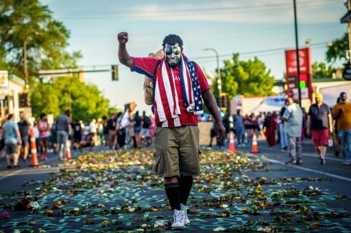 A man raises his fist during a memorial for George Floyd after a day of demonstrations on June 7, 2020 in Minneapolis