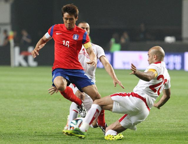South Korea's Koo Jacheol, left, fights for the ball against Tunisia's Stephane Houcine Nater and Aymen Abdennour, right, during their friendly soccer match at World Cup stadium in Seoul, South Korea, Wednesday, May 28, 2014. South Korea will play against Belgium, Russia and Algeria in Group H of the World Cup 2014 in Brazil. (AP Photo/Ahn Young-joon)