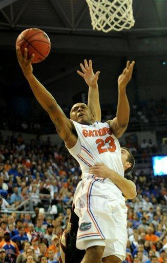 Florida's Bradley Beal (23) goes up for two points with Florida State's Luke Loucks hanging onto him during the first half of an NCAA college basketball game in Gainesville, Fla., Thursday, Dec. 22, 2011. (AP Photo/ Phil Sandlin)