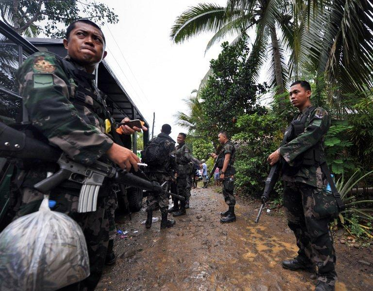 Members of a police special action force man a checkpoint in the southern Philippines on December 12, 2009