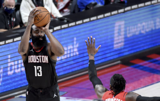 Houston Rockets guard James Harden shoots over Portland Trail Blazers forward Robert Covington during the second half of an NBA basketball game in Portland, Ore., Saturday, Dec. 26, 2020. The Blazers won 128-126 in overtime. (AP Photo/Steve Dykes)