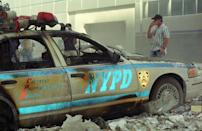 An NYPD officer stands by the wreckage of a police patrol vehicle. (Caters)