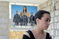 Karlen Hitti Karam's husband, brother and cousin -- picture behind her -- were firefighters killed in the Beirut blast that claimed 214 lives