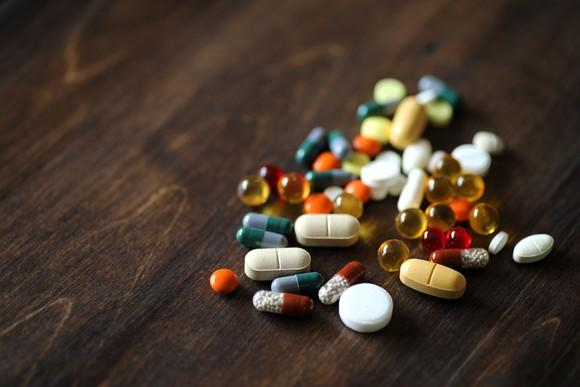 Many different types of supplements on a wood table.