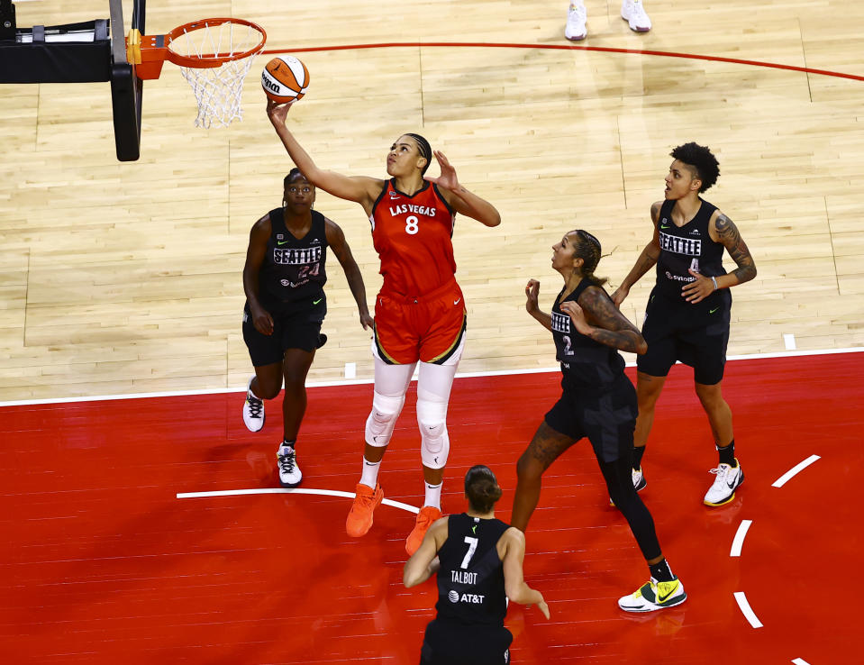 Las Vegas Aces' Liz Cambage (8) goes to the basket between Seattle Storm's Jewell Loyd (24) and Mercedes Russell (2) during the first quarter of a WNBA basketball game at Michelob Ultra Arena on Sunday, June 27, 2021, in Las Vegas. (Chase Stevens/Las Vegas Review-Journal via AP)
