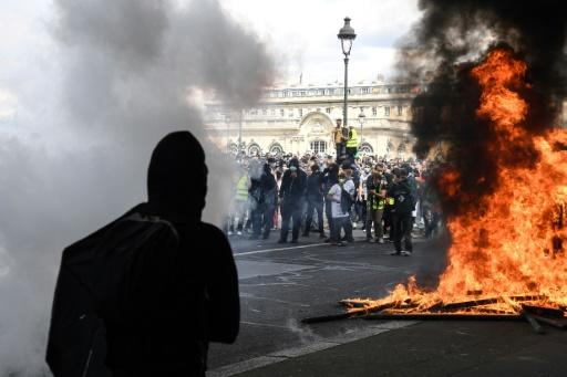 """Protesters clad in black set fire to a vehicle and pelted the police with projectiles, chanting """"everybody hates the police"""""""