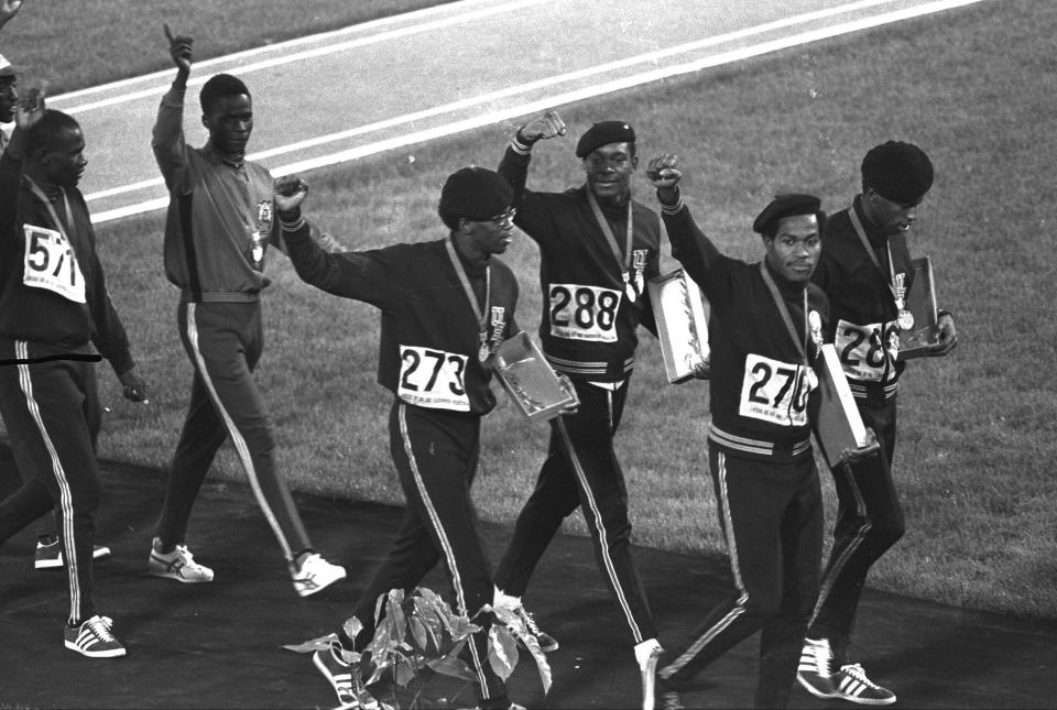 FILE - Three out of four members of the United States 4x400-meter relay team, right, hold up clenched fists as they leave the Olympic stadium after receiving their gold medals during the Mexico City Games in Mexico City, in this Sunday Oct. 21, 1968, file photo. The four, from left, are Ron Freeman (273), Vince Matthews, Lee Evans and Larry James. Lee Evans, the record-setting sprinter who wore a black beret in a sign of protest at the 1968 Olympics, died Wednesday, May 19, 2021. He was 74. USA Track and Field confirmed Evans' death. The San Jose Mercury News reported that Evans' family had started a fundraiser with hopes of bringing him back to the U.S. from Nigeria, where he coached track, to receive medical care after he suffered a stroke last week.(AP Photo/File)