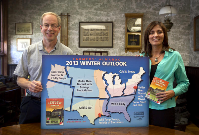 """In this photo made Thursday, Aug. 23, 2012, Farmers' Almanac publisher Peter Geiger, left, and editor Sondra Duncan pose in Lewiston, Maine, with a map showing the predicted weather forecast for the United States. In an election year, the almanac dubs its forecast """"a nation divided"""" because there's a dividing line where winter returns for much of the east, with milder weather west of the Great Lakes. (AP Photo/Robert F. Bukaty)"""