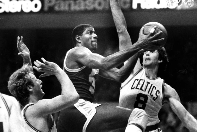 BOSTON, MA - MAY 27: Los Angeles Lakers' Magic Johnson splits the defense of Celtics' Larry Bird, left, and Scott Wedman to score two points in Game One of the 1985 NBA Finals between the Boston Celtics and the Los Angeles Lakers at the Boston Garden on May 27, 1985. (Photo by George Rizer/The Boston Globe via Getty Images)