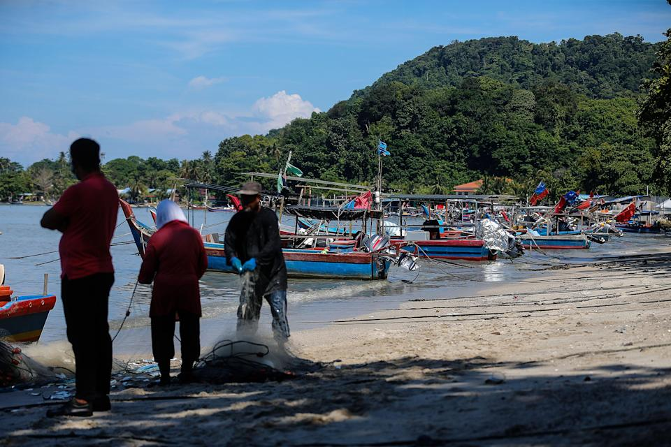 Fishermen are pictured mending their nets at Bayan Lepas June 16, 2021. The the DOSM said the reduction of fish landing is due to a decrease in the number of vessels operating at sea because of the shortage in foreign labour. — Picture by Sayuti Zainudin