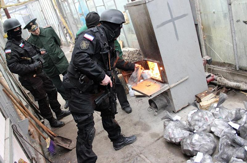 Russian Federal Drug Control Service officers burn bags of synthetic opioid Methadone during an operation in Simferopol on December 23, 2014 (AFP Photo/Yuri Lashov)