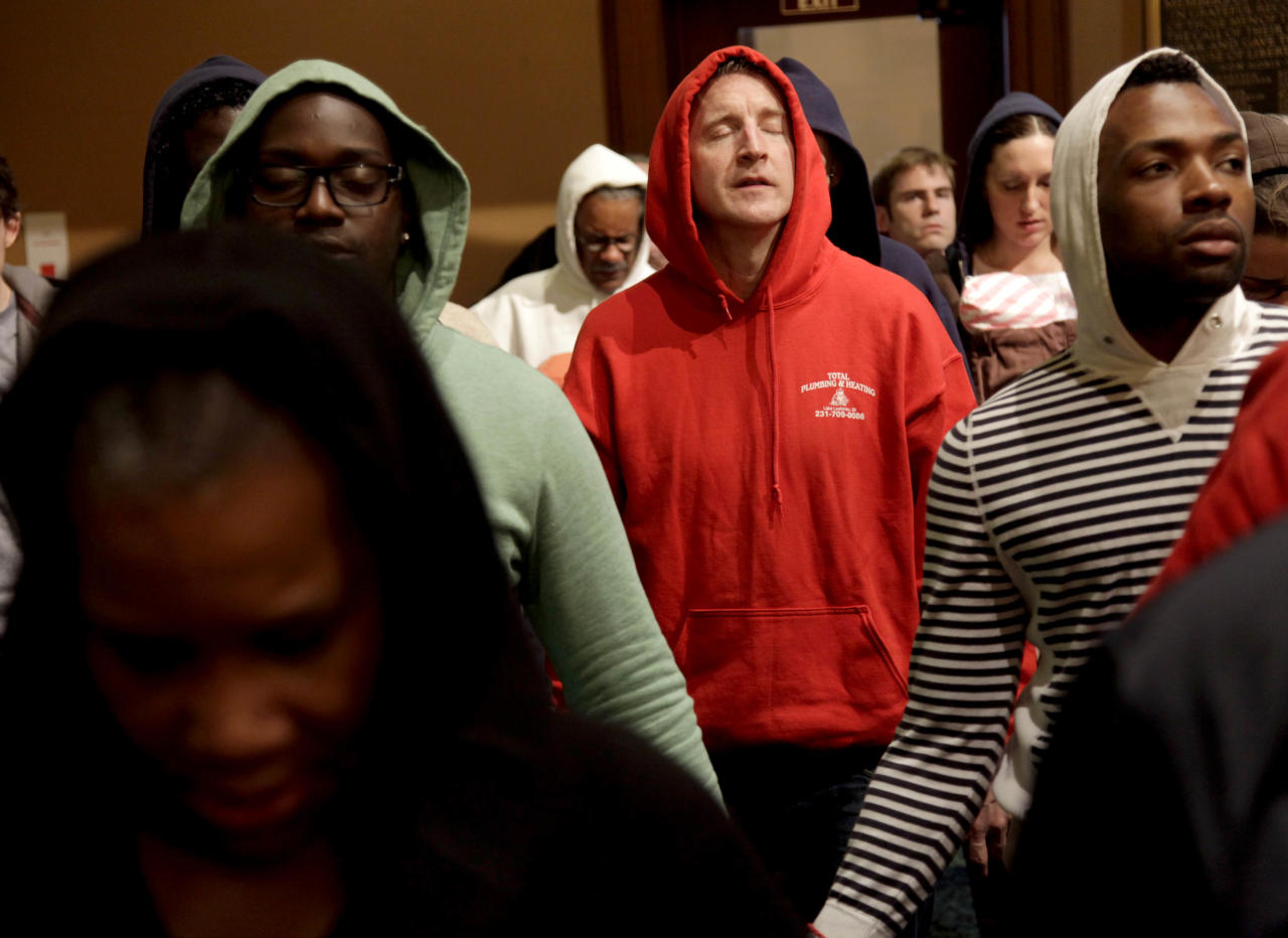 Patrick Mulchay, center, joins other congregants in song during a service at Middle Collegiate Church in New York, Sunday, March 25, 2012. Church-goers were invited to wear hoodies to services to show their support for justice in the case of Trayvon Martin, an unarmed black teenager who was wearing a hoodie on the night he was killed by a neighborhood watch captain in Florida. (AP Photo/Seth Wenig)
