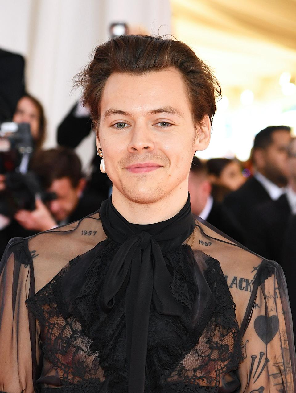 Harry Styles stuns on a red carpet show in black see-through blouse with a bow at the neck area