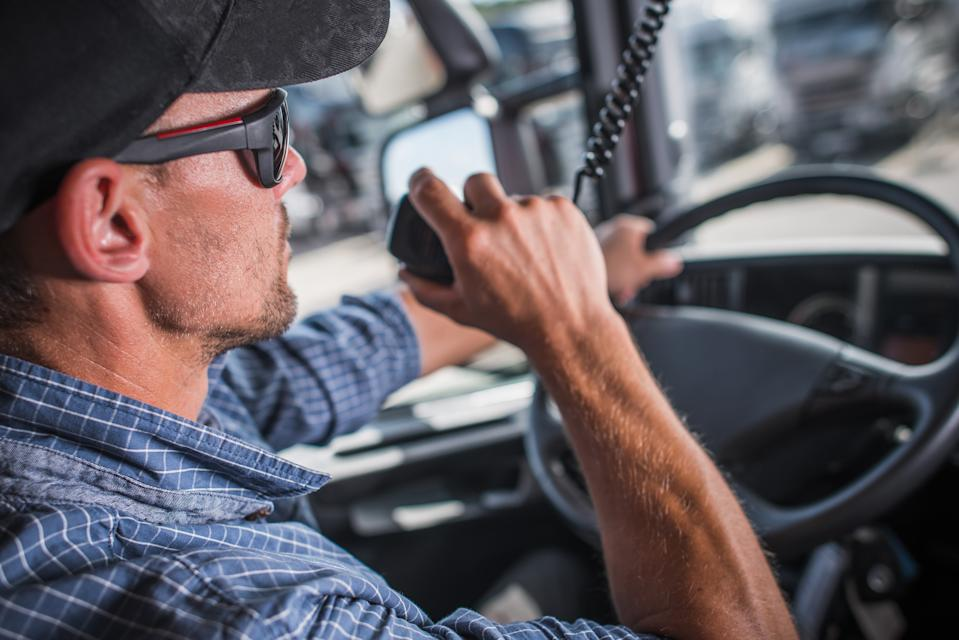 Caucasian Truck Driver in his 30s CB Talking with Other Drivers in the Convoy. Heavy Load Transportation Communication.