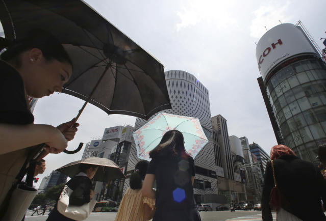 <p>People shade themselves from the heat of the sun with umbrellas as they pass the Ginza shopping district in Tokyo, July 23, 2018. (Photo: Koji Sasahara/AP) </p>