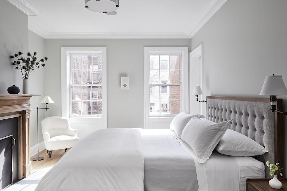 The main bedroom sets a soothing tone with a custom bed upholstered in Larsen fabric opposite the restored fireplace, custom walnut bedside tables, and a chair from John Derian. The sconces are by Ann-Morris, and the rug is by Holland & Sherry.