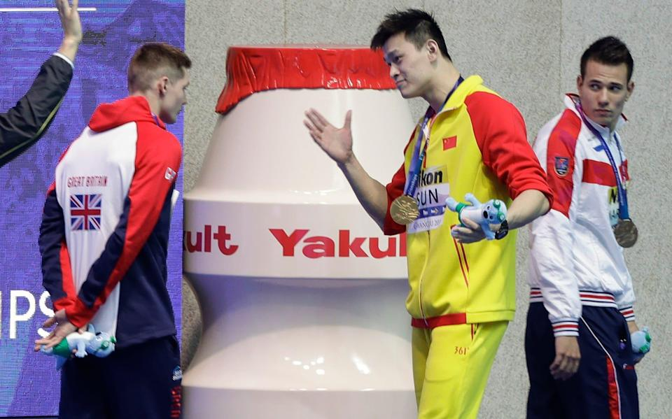 China's Sun Yang, centre, gestures to Britain's bronze medalists Duncan Scott, left, following the medal ceremony in the men's 200m freestyle final at the World Swimming Championships in Gwangju, South Korea. Chinese swimmer Sun Yang has been banned for eight years for breaking anti-doping rules and will miss the 2020 Tokyo Olympics - AP Photo/Mark Schiefelbein