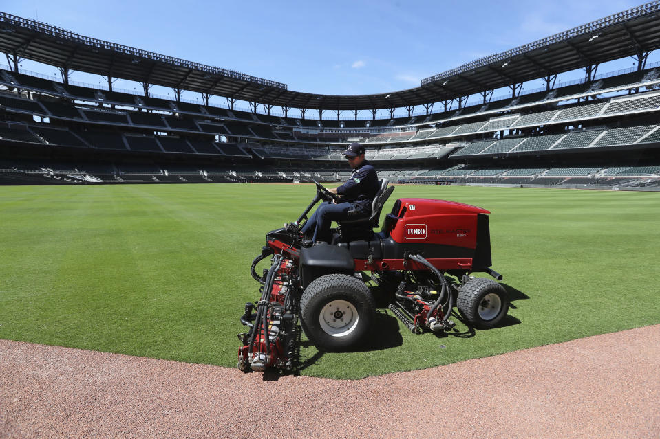 Atlanta Braves field manager Anthony DeFeo mows the grass in the outfield in the team's newly renamed Truist Park on Wednesday, April 1, 2020, in Atlanta. The Braves were supposed to host their home opener this Friday, but the season's start was postponed by Major League Baseball because of the coronavirus pandemic. (Curtis Compton/Atlanta Journal-Constitution via AP)