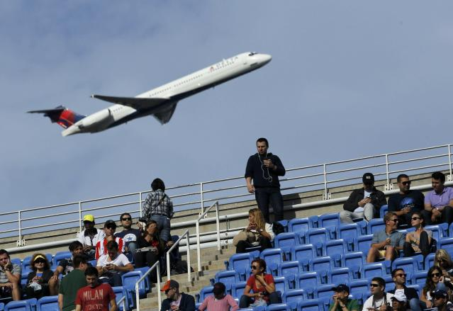 An airliner takes off from nearby LaGuardia Airport as spectators watch as Rafael Nadal of Spain faces Novak Djokovic of Serbia in the men's final match at the U.S. Open tennis championships in New York, September 9, 2013. REUTERS/Kena Betancur (UNITED STATES - Tags: SPORT TENNIS TRANSPORT)