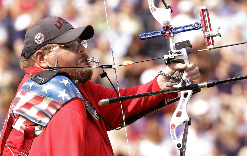 Eric Bennett of the United States prepares to fire an arrow at man's archery individual recurve standing bronze medal match at the 2012 Paralympics games, Monday, Sept. 3, 2012, in London. Bennett who shoots using his mouth to fire the arrows missed out on the bronze medal that was won by Mikhail Oyun of Russia. (AP Photo/Alastair Grant)