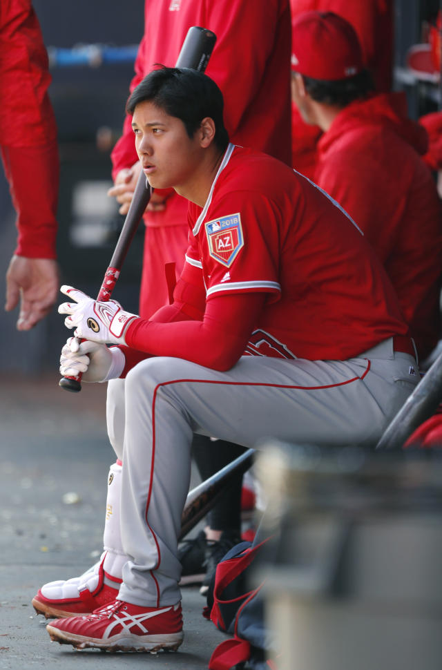 Los Angeles Angels' Shohei Ohtani sits in the dugout during the second inning of a spring training baseball game against the San Diego Padres, Monday, Feb. 26, 2018, in Peoria, Ariz. (AP Photo/Charlie Neibergall)