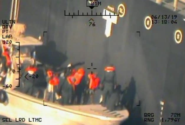 This image, taken from a U.S. Navy helicopter, shows what the Navy says are members of the Islamic Revolutionary Guard Corps Navy removing an unexploded mine from the ship Kokuka Courageous. (Photo: U.S. Department of Defense via AP)
