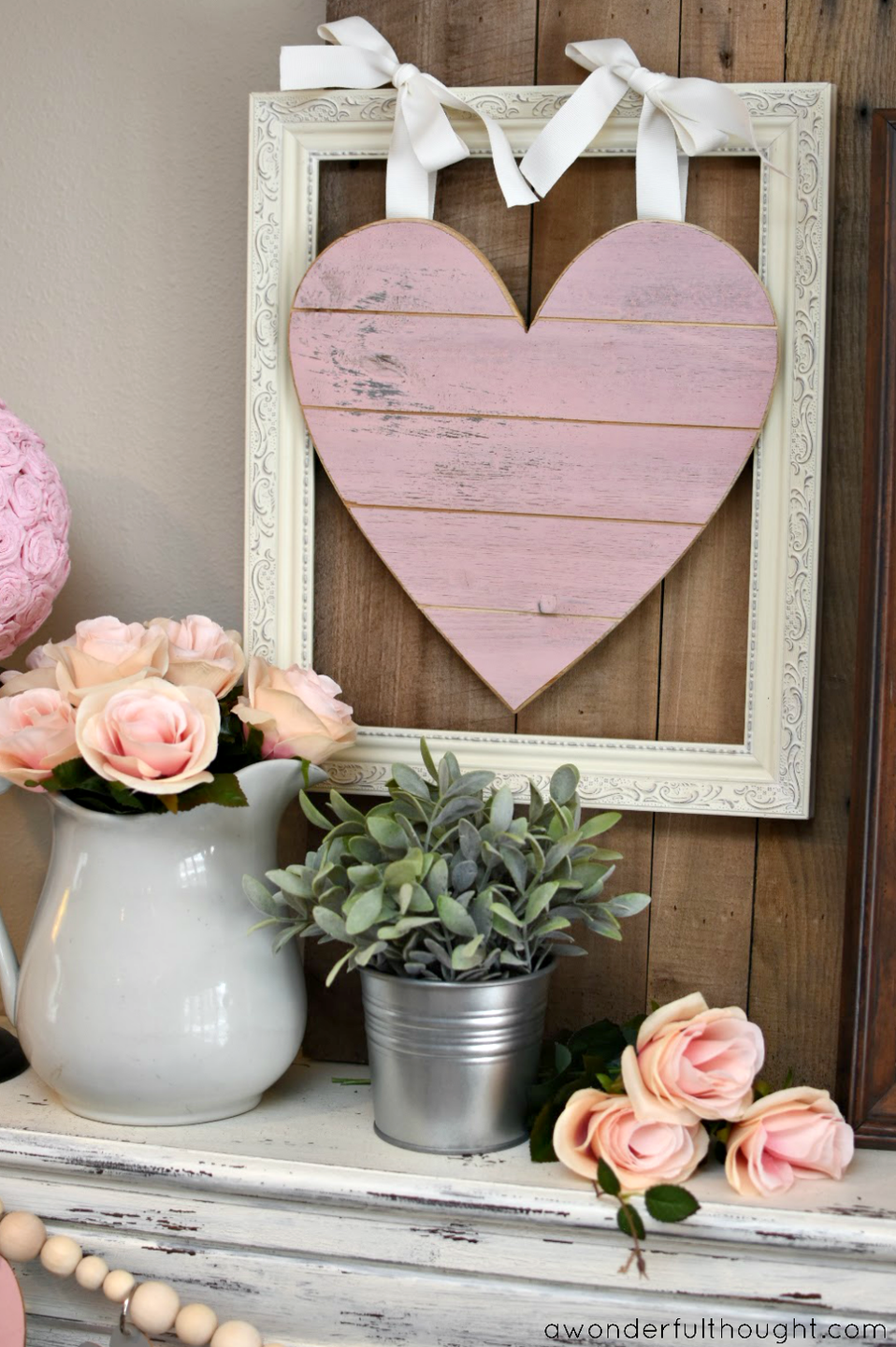 """<p>A framed heart made of shiplap and vases of faux flowers serve as the focal point for this beautiful Valentine's Day mantel display.</p><p><strong>Get the tutorial at <a href=""""http://awonderfulthought.com/pretty-pink-gray-valentines-day-mantel/"""" rel=""""nofollow noopener"""" target=""""_blank"""" data-ylk=""""slk:A Wonderful Thought"""" class=""""link rapid-noclick-resp"""">A Wonderful Thought</a>.</strong></p><p><strong><a class=""""link rapid-noclick-resp"""" href=""""https://www.amazon.com/slp/wood-heart-wall-decor/uv2r7uzb6zwxo92?tag=syn-yahoo-20&ascsubtag=%5Bartid%7C10050.g.2971%5Bsrc%7Cyahoo-us"""" rel=""""nofollow noopener"""" target=""""_blank"""" data-ylk=""""slk:SHOP HEART DECOR"""">SHOP HEART DECOR</a><br></strong></p>"""