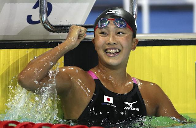 Kanako Watenabe of Japan raises her fist as she celebrates winning he women's 200m breaststroke final at the Pan Pacific swimming championships in Gold Coast, Australia, Sunday, Aug. 24, 2014. Watenabe won the race ahead of team mate Rie Kaneto and Taylor McKeown of Australia.(AP Photo/Rick Rycroft)