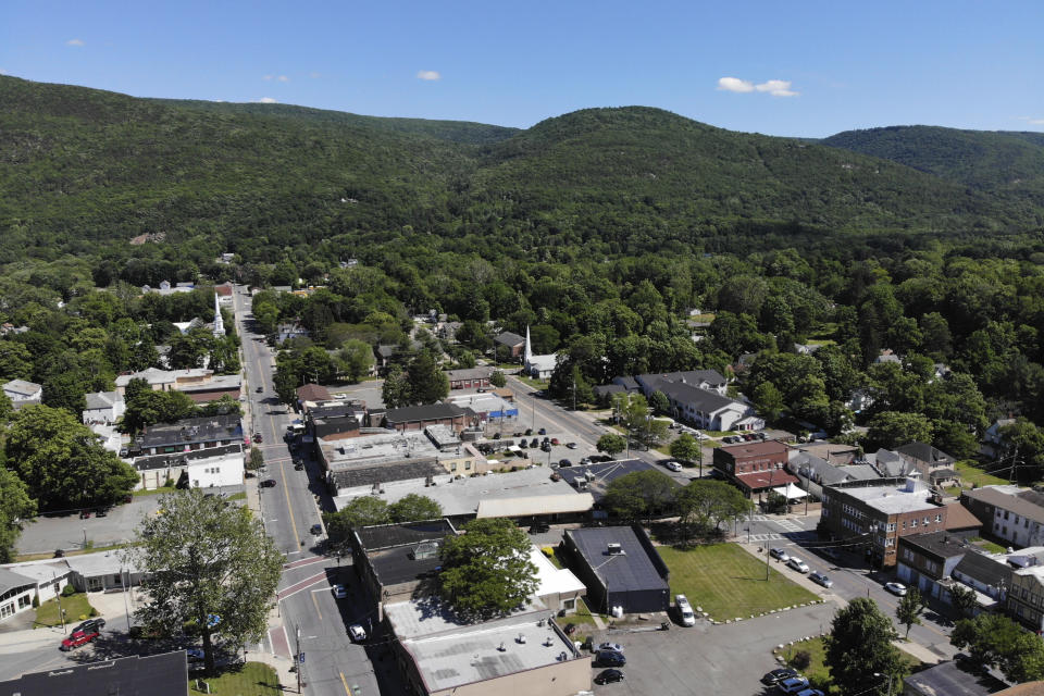 Surrounded by trees and mountains, Ellenville, N.Y., is seen Wednesday, June 16, 2021. Less than 100 miles north of New York City, Ulster County is popular destination for weekenders headed to Woodstock or the Catskill Mountains. Though pretty, there are pockets of poverty. The county is working with the Center for Guaranteed Income Research at the University of Pennsylvania on a pilot program funded by private donations. One hundred households making less than $46,900 a year in May began receiving a $500 payment each month for a year. Recipients of the money can spend it as they wish, but will be asked to participate in periodic surveys about their physical health, mental health and employment status. (AP Photo/Seth Wenig)