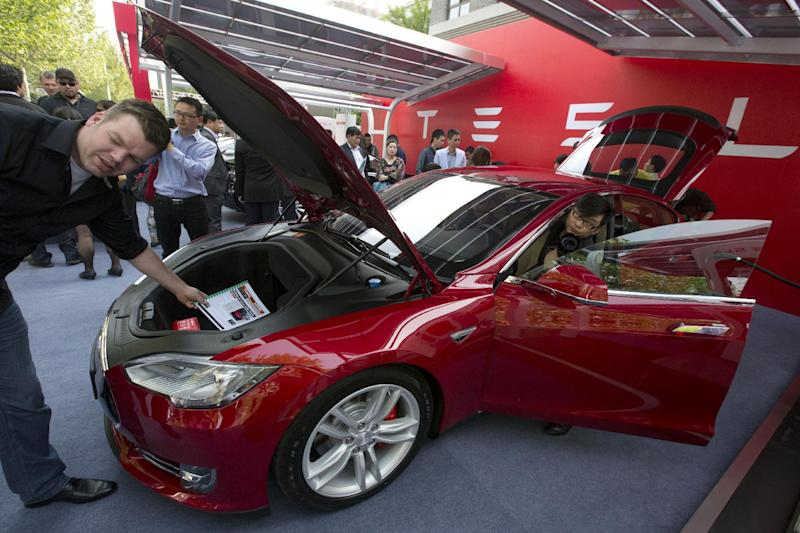 Customers and journalists examine a Tesla Model S sedan at an event in Beijing, China, Tuesday, April 22, 2014. Tesla Motors delivered its first eight electric sedans to customers in China on Tuesday and Musk said the company will build a nationwide network of charging stations and service centers as fast as it can. (AP Photo/Ng Han Guan)