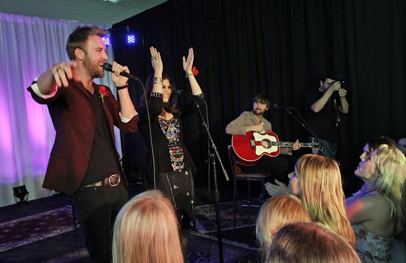 "Lady Antebellum's Charles Kelley, Hillary Scott and Dave Haywood perform for Henryville High School students Wednesday, May 16, 2012, in Louisville, Ky. The Grammy-winning trio staged a ""mini-prom"" bash for students from Henryville Junior-Senior High School, followed by a benefit for the community devastated by a March 2 tornado. (AP Photo/Darron Cummings)"