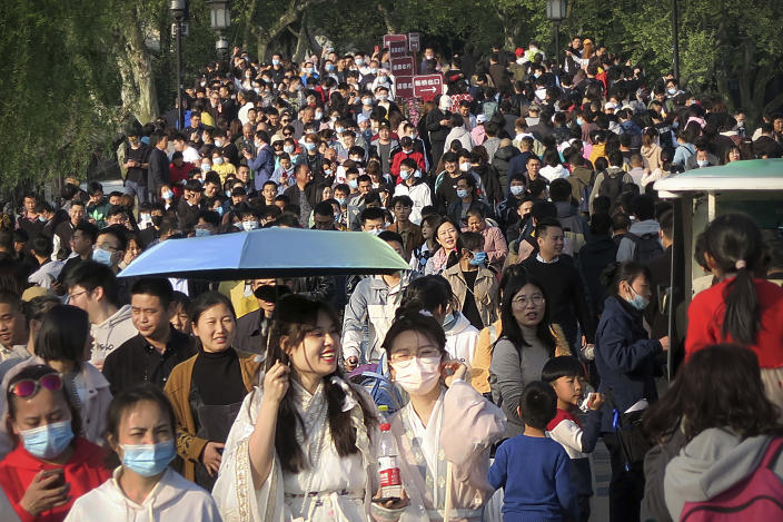 Visitors wearing face masks to protect against COVID-19 walk across a causeway at the West Lake in Hangzhou in eastern China's Zhejiang Province, Sunday, April 4, 2021. Domestic tourists were out in force at some of China's most popular tourist sites on a holiday weekend as the country continues to report few new cases of coronavirus within its borders. (AP Photo/Mark Schiefelbein)
