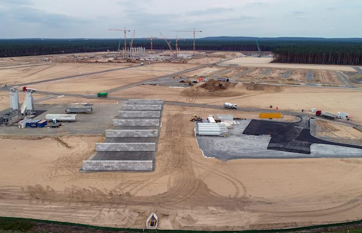 15 July 2020, Brandenburg, Grünheide: Cranes and first piers for the future Tesla Giga-Factory can be seen on the construction site (aerial view with a drone). In Grünheide near Berlin, a maximum of 500,000 vehicles per year are to roll off the assembly line from July 2021 - and according to the car manufacturer's plans, the maximum should be reached as quickly as possible. The US electric car manufacturer expects up to 10,500 employees working in shifts for its planned first factory in Europe.