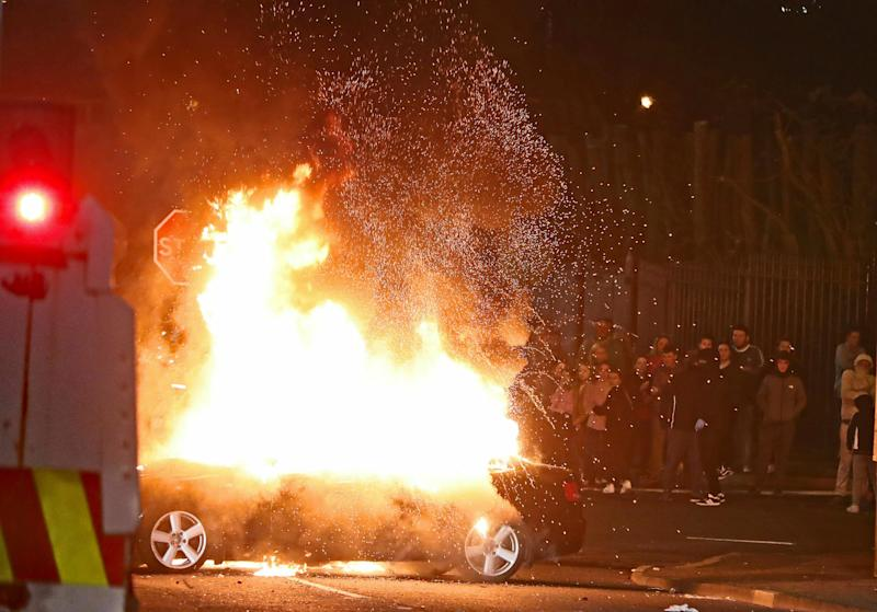 Crowds watch on as a car goes up in flames. Source: AAP