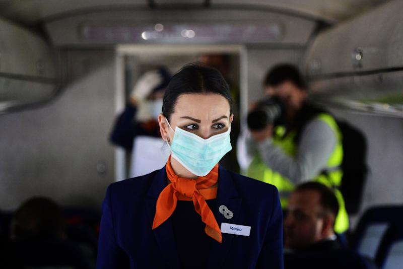 Put on your mask first before assisting others. (Photo: Yuri Smityuk via Getty Images)