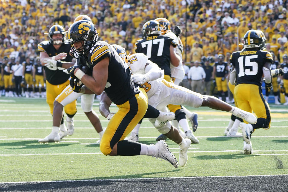 Iowa tight end Sam LaPorta (84) catches a 5-yard touchdown pass ahead of Kent State linebacker Mandela Lawrence-Burke (28) during the first half of an NCAA college football game, Saturday, Sept. 18, 2021, in Iowa City, Iowa. (AP Photo/Charlie Neibergall)