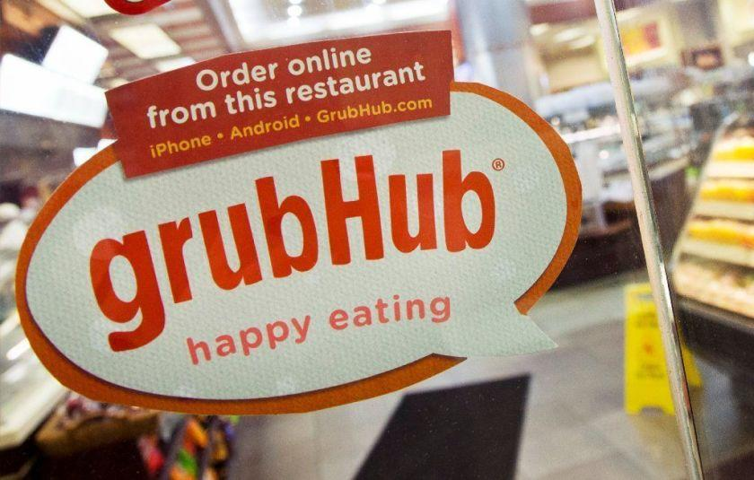 FILE - In this April 4, 2014 file photo, a sign for GrubHub is displayed on the door to a New York restaurant. The owner of KFC and Taco Bell, is teaming up with Grubhub to expand its delivery business. Yum Brands said Thursday, Feb. 8, 2018, that Grubhub will run KFC and Taco Bell delivery and online ordering in the United States. GrubHub will provide delivery people and its technology.(AP Photo/Mark Lennihan, File)