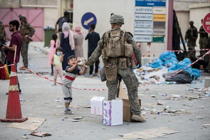 A Marine with the 24th Marine Expeditionary Unit (MEU) provides a meal ready-to-eat to a child during an evacuation at Hamid Karzai International Airport, Kabul, Afghanistan, Aug. 20