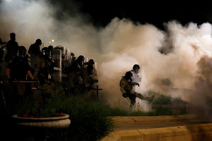 Image: Officers stand in a cloud of tear gas as protesters retreat on the steps of the Iowa State Capitol on May 30, 2020 in Des Moines. (Brian Powers / The Register via USA-Today Network)