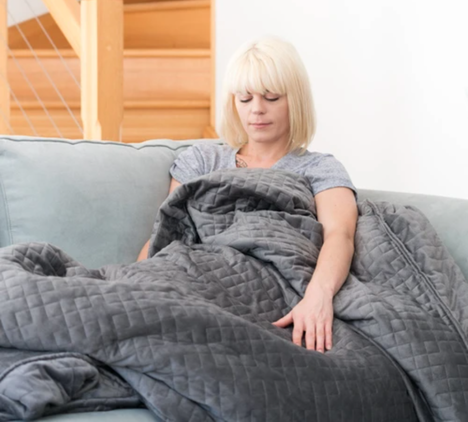 woman sitting on a couch with a weighted blanket