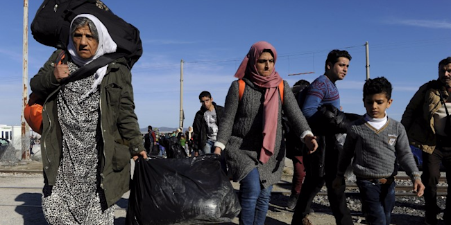 Migrants carry their belongings inside a camp, as they wait to cross the Greek-Macedonian border, near the village of Idomeni, Greece, February 2, 2016. REUTERS/Alexandros Avramidis