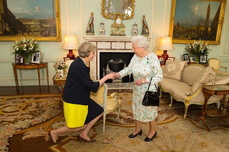 The new leader of the Conservative Party Theresa May (L) kneels as she is greeted by Britain's Queen Elizabeth II (R) at the start of an audience in Buckingham Palace in central London on July 13, 2016 (AFP Photo/Dominic Lipinski)