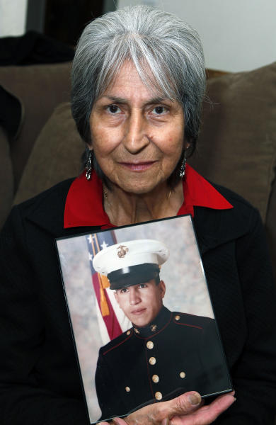 In this Oct. 5, 2012, photo Delouise Guerra poses for a photo in Denver with a 1975 photo of her younger brother,18-year-old Marine PFC James Jacques who was killed in a helicopter crash near Cambodia in 1975. Jacques remains were identified in August of this year. He will be buried with full military honors at Fort Logan National Cemetery in Denver on Tuesday, Oct. 9, 2012, on what would have been his 56th birthday.(AP Photo/Ed Andrieski)